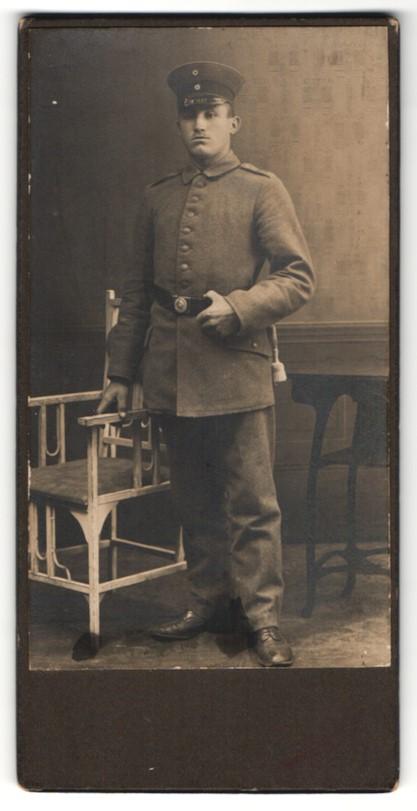 Fotografie Soldat in feldgrauer Uniform mit Mütze 0