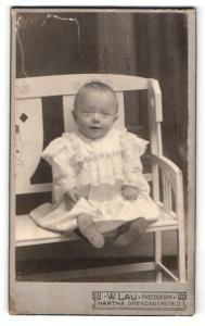 Fotografie W. Lau, Hartha, Portrait lachendes süsses Kleinkind im weissen bestickten Kleidchen