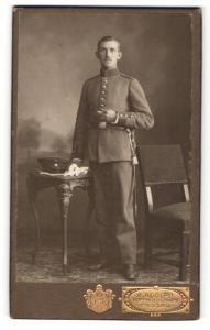 Fotografie A. Adolph, Passau, Portrait Soldat in Uniform an Tisch gelehnt