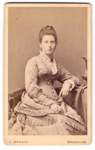 Fotografie C. Brasch, Berlin-W, Portrait junge Dame im eleganten Kleid am Tisch sitzend