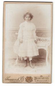 Fotografie Samson & Co., Dortmund, Portrait hübsches Mädchen mit Locken im weissen Kleid