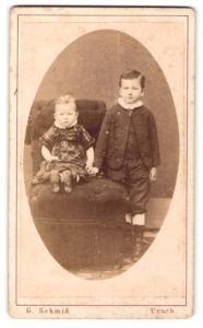 Fotografie G. Schmid, Urach, Portrait kleines Mädchen im karierten Kleid auf Sessel sitzend u. Bruder