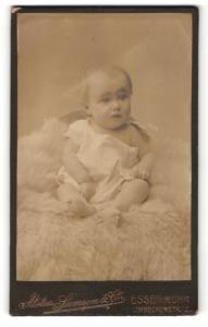 Fotografie Samson & Co, Essen-Ruhr, Portrait niedliches Baby im weissen Hemd auf Fell sitzend