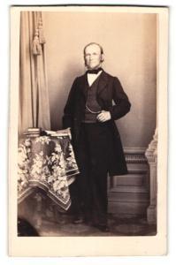 Fotografie W. Jab, Berlin, Portrait bürgerlicher Herr im Anzug mit Buch an Tisch gelehnt