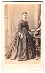 Fotografie Carl Zimmermann, Berlin, Portrait junge Dame im festlichen Kleid mit Buch an Tisch gelehnt