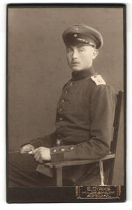 Fotografie E. Dirks, Hildesheim, Alfeld a / L., Portrait Soldat in Uniform mit Schirmmütze auf Stuhl sitzend