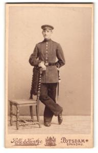 Fotografie Selle & Kuntze, Potsdam & Berlin-Spandau, Portrait Soldat in Uniform mit Schirmmütze an Stuhl gelehnt
