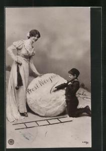 AK Schornsteinfeger, Junge schreibt auf Schneekugel Prost Neujahr, elegante Frau daneben