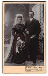 Fotografie E. Ostenkötter, Hirschfelde & Ostritz, Portrait bürgerliches Paar in hübscher Hochzeitskleidung mit Blumen