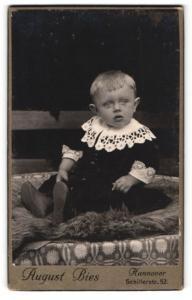 Fotografie August Bies, Hannover, Portrait blonder niedlicher Bube im bestickten Hemdchen