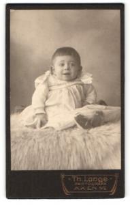 Fotografie Th. Lange, Aken a. E., Portrait lachendes Kleinkind im weissen Kleidchen auf Fell sitzend