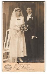 Fotografie G. S. Ander, Lidköping, Portrait bürgerliches Paar in hübscher Hochzeitskleidung mit Schleier u. Blumenstrauss