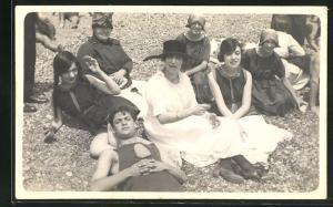 Foto-AK Damen sitzen mit einem Herrn im Badeanzug am Strand