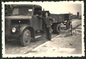 Fotografie Lastwagen, Fahrer lehnt an LKW-Pritsche mit Anhänger