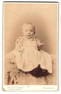 Fotografie Fritz Küken, Bielefeld, Portrait blondes niedliches Kleinkind im Schleifen-Kleidchen