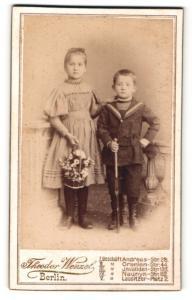 Fotografie Theodor Wenzel, Berlin, Portrait bezauberndes Kinderpaar in hübscher Kleidung mit Blumenkob