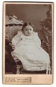Fotografie J. Fuchs, Berlin-Charlottenburg, Portrait niedliches Kleinkind im hübschen Kleid auf Stuhl sitzend