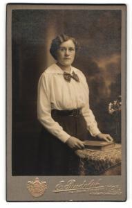 Fotografie E. Rudolph, Hof, Portrait brünette junge Frau mit Buch und Schleife am Kragen