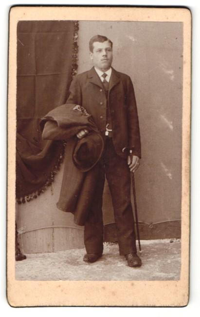 Fotografie Franz Sternath, München, Portrait Herr im Anzug mit Hut, Stock u. Mantel unterm Arm 0