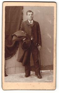 Fotografie Franz Sternath, München, Portrait Herr im Anzug mit Hut, Stock u. Mantel unterm Arm