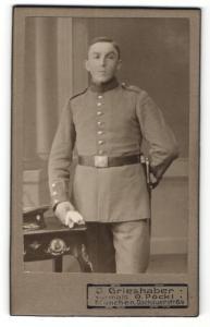 Fotografie J. Grieshaber, München, Portrait Soldat in Uniform mit Handschuhen an Tisch gelehnt