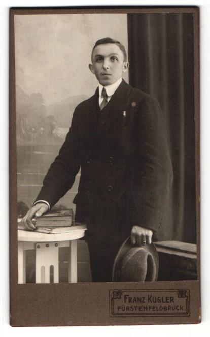 Fotografie Franz Kugler, Fürstenfeldbruck, Portrait Herr im Anzug mit Hut u. Büchern an Tisch gelehnt 0