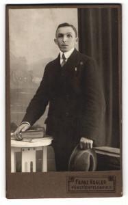 Fotografie Franz Kugler, Fürstenfeldbruck, Portrait Herr im Anzug mit Hut u. Büchern an Tisch gelehnt