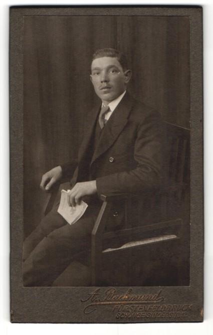 Fotografie A. Backmund, Fürstenfeldbruck, Portrait Herr im Anzug mit Buch auf Stuhl sitzend 0