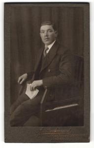 Fotografie A. Backmund, Fürstenfeldbruck, Portrait Herr im Anzug mit Buch auf Stuhl sitzend
