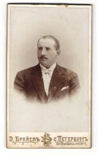 Fotografie unbekannter Fotograf, St. Petersburg, Portrait charmanter Herr mit Zwirbelbart u. Fliege im Anzug