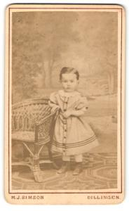 Fotografie M. J. Simson, Dillingen, Portrait kleines Mädchen im hübschen Kleid an Stuhl gelehnt