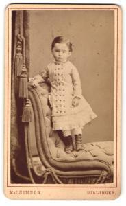 Fotografie M. J. Simson, Dillingen, Portrait kleines Mädchen im hübschen Kleid auf Sessel stehend
