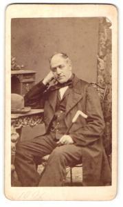 Fotografie Franz Neumayer, München, Portrait bürgerlicher Herr im Anzug mit Stock am Schreibtisch sitzend