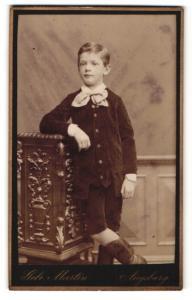 Fotografie Gebr. Martin, Augsburg, Portrait kleiner Junge in hübscher Kleidung an Sockel gelehnt