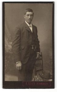 Fotografie A. Adler, Memmingen, Portrait charmanter Herr mit Fliege im Anzug an Stuhl gelehnt