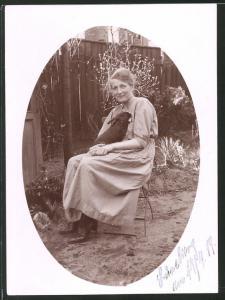 Fotografie Ostergruss, hübsche Dame kuschelt mit Kaninchen um 1919