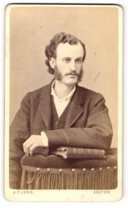 Fotografie J. F. Long, Exeter, Portrait Herr mit Backenbart im Anzug auf Lehne gestützt