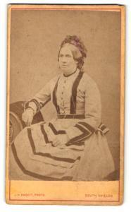 Fotografie J. H. Haggit, South Shields, Portrait ältere Dame mit Haube im modischen Kleid auf