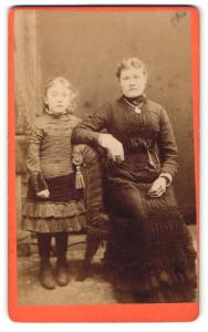 Fotografie Pfairclough Stanhope, Newcastle, Frau im Kleid mit Halskette sitzend und Mädchen im Kleid stehend