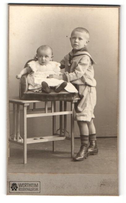 Fotografie Atelier Wertheim, Berlin, Junge im Pfadfinderkleidung stehend und Baby im Kinderstuhl sitzend 0