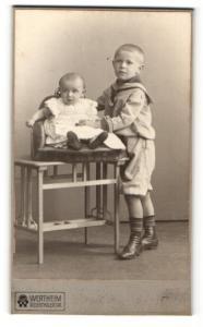 Fotografie Atelier Wertheim, Berlin, Junge im Pfadfinderkleidung stehend und Baby im Kinderstuhl sitzend