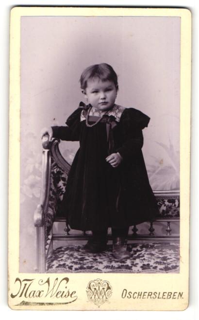 Fotografie Max Weise, Oschersleben, kleines Mädchen in dunklem Kleid auf Bank stehend 0