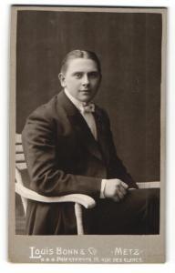 Fotografie Louis Bonn & Co., Metz, junger Mann im Stuhl sitzend mit leichtem Lächeln