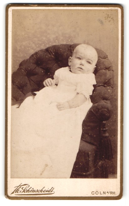 Fotografie Th. Schönscheidt, Cöln, Baby im Taufkleid auf Sessel liegend 0