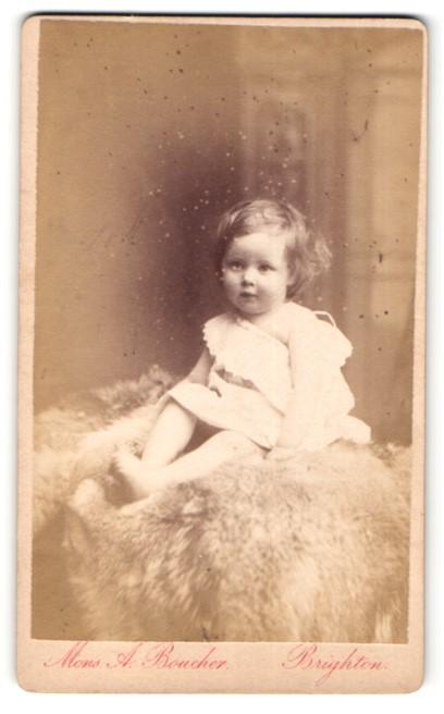 Fotografie Monsieur A. Boucher, Brighton, Baby im Kleidchen auf Pelzdecke sitzend 0