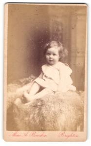 Fotografie Monsieur A. Boucher, Brighton, Baby im Kleidchen auf Pelzdecke sitzend