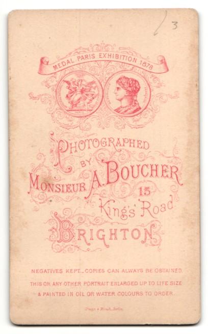 Fotografie Monsieur A. Boucher, Brighton, Baby im Kleidchen auf Pelzdecke sitzend 1