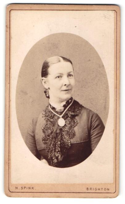 Fotografie H. Spink, Brighton, Frau im Kleid mit Halskette und Amulett daran 0