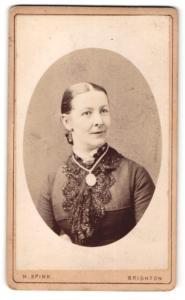 Fotografie H. Spink, Brighton, Frau im Kleid mit Halskette und Amulett daran