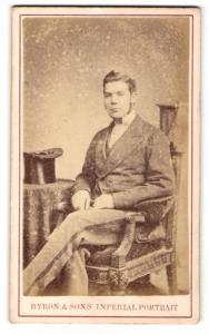 Fotografie Byron & Son`s, Nottingham, Mann mit Kotletten im Anzug auf Stuhl sitzend
